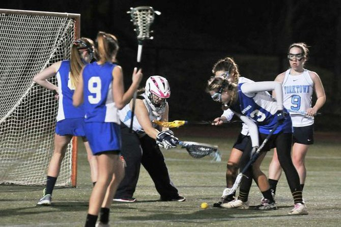 West Potomac senior Karley Zdebski, right, looks to scoop the ball off the turf during Monday nights game at Yorktown.