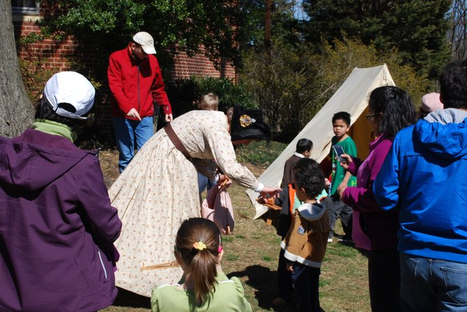 "Kecia Wolf, a Fairfax resident and school social worker in Prince William County, demonstrates her period-correct ""pecking hen"" toys with a couple of young historians. Wolf volunteers with the 17th Virginia Infantry Fairfax Rifles and appeared as Joshua Gunnell's civilian wife, who is credited with distracting Confederate soldiers during the raid while her husband fled under the family house."