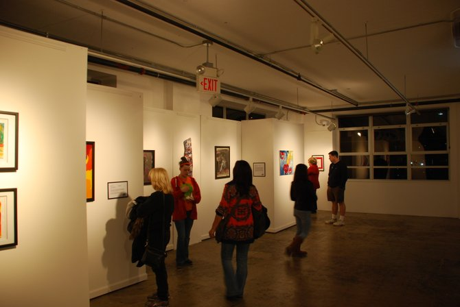 Visitors examine the mixed media artworks created by survivors of sexual and domestic violence.