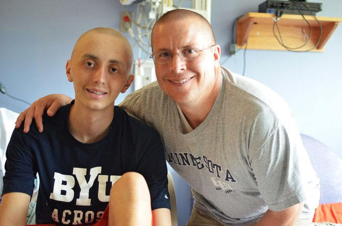 (From left) are Spencer Goold and dad Glen during Spencer's treatment. His dad and a dozen friends shaved their heads in solidarity with Spencer when he lost his hair to chemo.