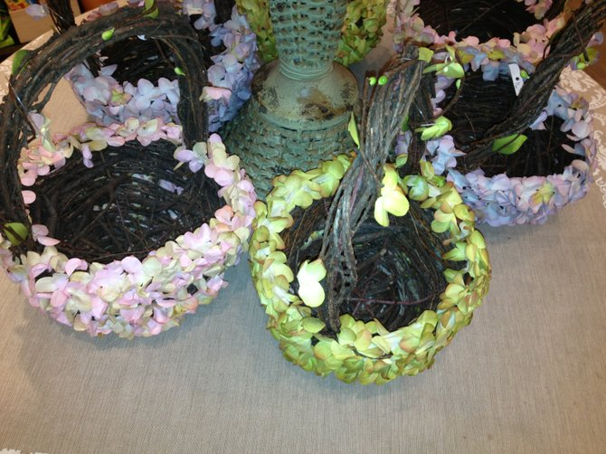 A floral arrangement displayed in baskets covered with spring flower petals makes a chic centerpiece for the dining table.