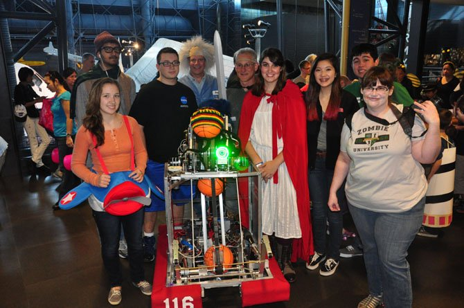 The Herndon High School Robotics team, pictures at an outreach event last year, will compete in a championship event in St. Louis this month.