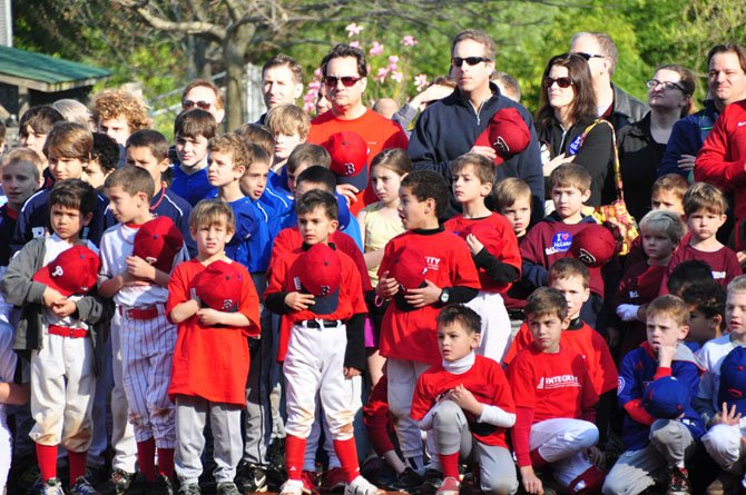 McLean Little League players and parents take a moment for the National Anthem during their opening day ceremony Saturday, April 13.