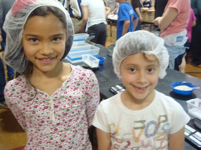 Sydney Guthrie and Kiara Wright, 7-year-olds and first graders at Louise Archer Elementary School, enjoyed working on Sunday, April 7, packaging meals for Stop Hunger Now.
