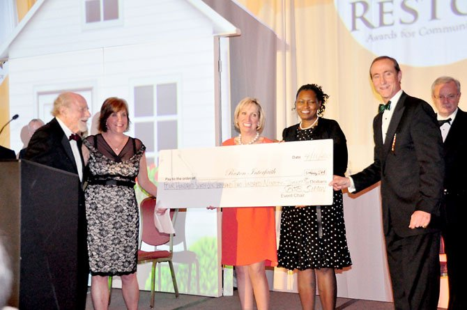From left, Reston founder Robert Simon, Reston Interfaith CEO Kerrie Wilson, Jane Raymond, chair-elect of the Greater Reston Chamber of Commerce, Angela Harpalani, chair of Reston Interfaith, and Mark Ingrao, president of the Greater Reston Chamber of Commerce present a check for $466,293, the money raised for Reston Interfaith at the 22nd annual Best of Reston awards.