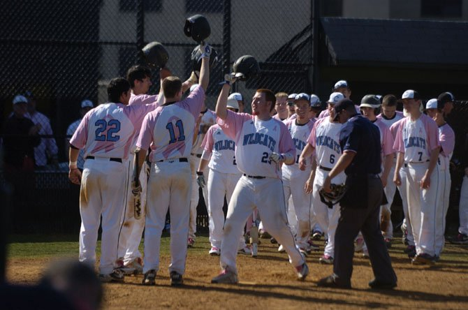 Members of the Centreville baseball team congratulate senior Matt Whalen (25) for hitting a three-run homer in the bottom of the sixth inning against Langley on April 13.