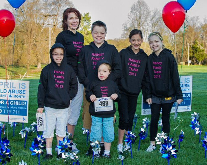 "SafeSpot founding board member and mom Bridget Rainey and members of The Rainey Family Team, all of Great Falls, huddle among the blue and silver pinwheels ""planted"" in the grass near the Champions4Children Race location at Lake Fairfax Park in Reston."