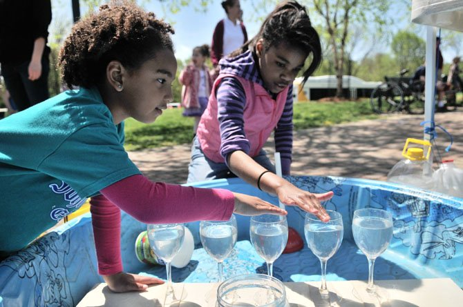 Paris Jones and Maya Gleaton listen as the water-filled wine glasses make different notes at one of the many children's activities at the 2013 Alexandria Earth Day in Ben Brenman Park.
