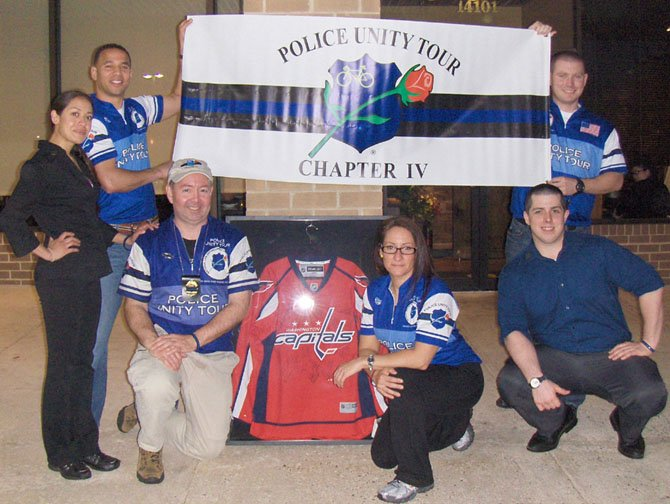City of Fairfax police participated in a Police Unity Tour fundraiser on Tuesday, April 16, at Coyote Grille in Centreville. Raffled off was this Washington Capitals jersey. Holding banner (back row, from left) are City of Fairfax Police Officers Robert Mignon (K-9) and Jay Tolan (patrol). (Front row, from left) are Christine Castro, Coyote Grille; federal agent Kevin Whalen; U.S. Park Police Officer Lisa Marie Weisbaum; and Randall Henderson, Coyote Grille.
