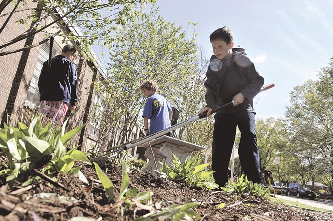 Asher Ager, Henry Wild and Quinn Bloom smooth out the piles of mulch just added to the front garden at Hollin Meadows.