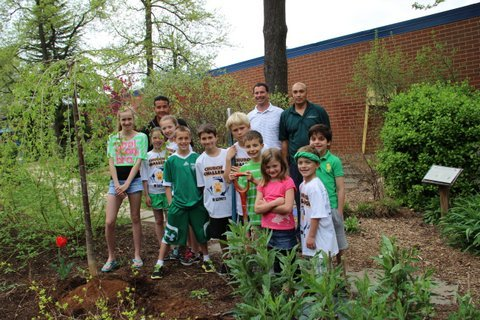 In honor of Earth Day, Churchill Road SCA representatives plant a weeping cherry tree donated by Wheat's Landscape.  Pictured, from left, are: SCA members Lauren Maloney, Liliana Schone, Izzy Schone, J.J. Bellaschi, Matthew Strong, Whit Walter, Ryan Jones, Jordan Rupli, Joseph Hoeymans and Sam Murad. Wheat's Certified Arborist Kane Ramsey (center back) and his crew worked with the students to plant the tree.
