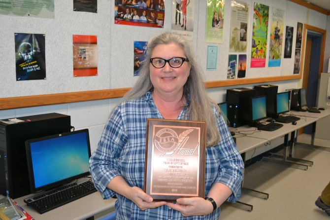 Longfellow Middle School teacher Helene Safford holds the 2012 Middle School Teacher of the Year Award.