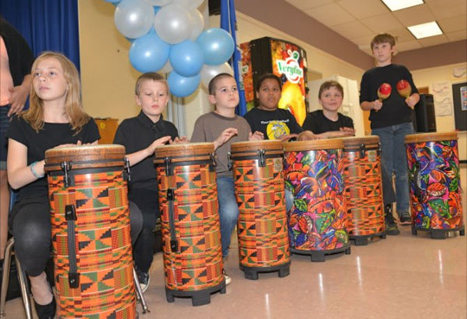 "Keeping the beat—the Dranesville Drumming Dragons provide the tempo for the chorus as they perform the South African hymn, ""Siyahamba."""
