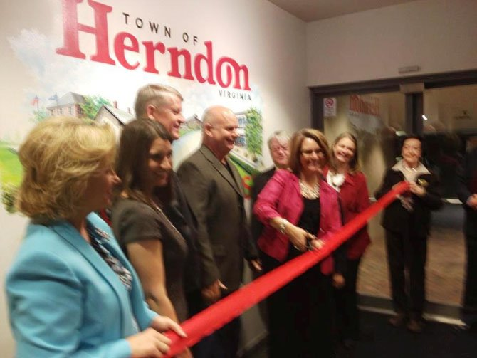 Mayor Lisa Merkel cuts the ribbon, formally accepting the mural, while CAH President Michael O'Reilly, artist Keith Naquin and members of the Herndon Town Council look on.