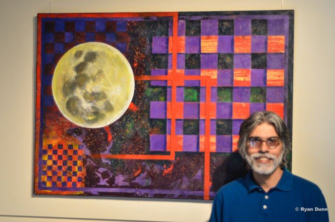 "Art instructor Arnold Lopes standing by his piece ""Flower Moon."""