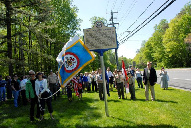 Braddock Supervisor John Cook (right) watches as Patty and Robert Kozak, descendants of the Union scout who planned the ambush, unveil the new historical marker commemorating the Bog Wallow Ambush of 1861.