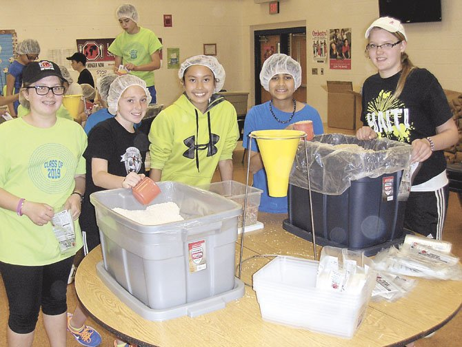 Scooping rice and soy protein into a funnel and then into a bag for packaging are (from left) Celie Anderson, Nicole Cohen, Samantha San, Akhil Havaldar and Katelin Bracewell.