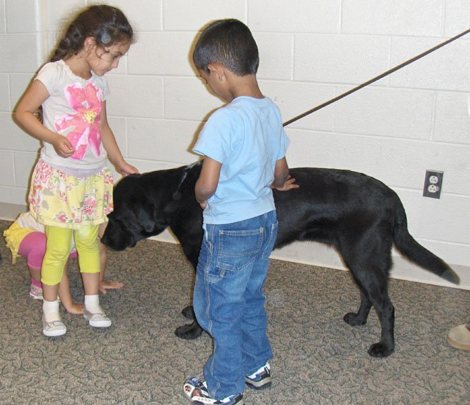 Children make friends with K-9 Spicey during the meeting.