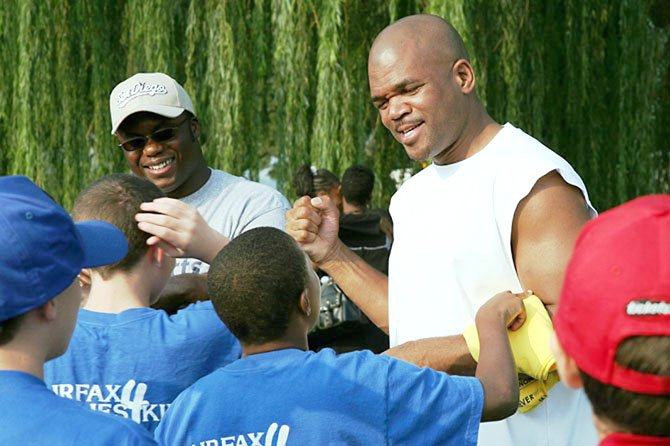 Pastor King Rhodes (left) has organized several 5K walks to benefit Fairfax Families4Kids, a mentoring program for foster youth. During the first fundraising walk in 2006, Rhodes enlisted the help of rapper Run DMC (right), who grew up in foster care.