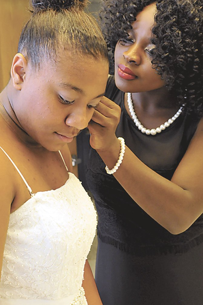 Genesis Taylor get help with an earring from Sento Bangura.