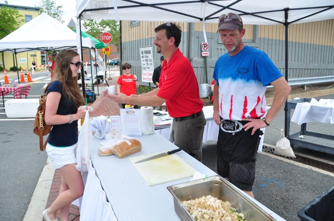 From right, Eric Quarnstrom and Jimmy Cirrito of Jimmy's Old Town Tavern hand out a sample of Jimmy's Chicken Stew to Lindsey Jones at the Herndon Farmer's Market Thursday, May 16.