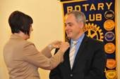 Laura Hills, president of The Rotary Club of Fairfax, pins a Rotary pin on GMU President Dr. Cabrera's lapel. The pin, a symbol of Rotary, was given to Dr. Cabrera during his induction as an honorary member of the club.