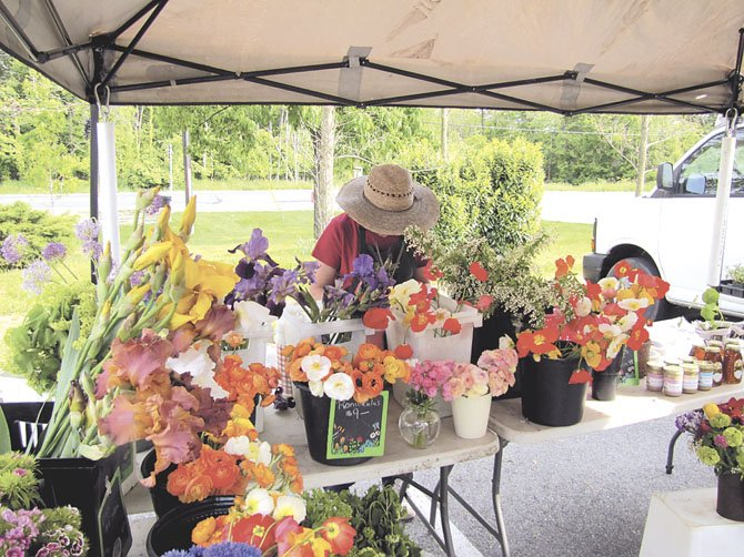 "Carol Carrier, of Plant Masters, lets the colors of her flowers do some of her advertising. Her merchandise will also be different throughout the time of the year. ""When you work at a farmer's market, you really eat well,"" she said."