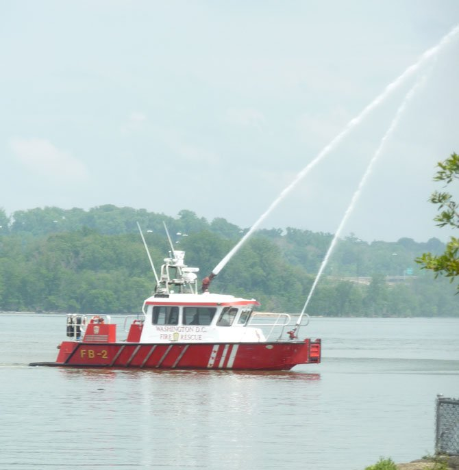 D.C. Fireboat John Glenn Jr. demonstrates a water cannon salute along the Potomac River as part of the 133rd annual flag raising at the Old Dominion Boat Club.