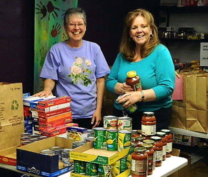 Debra Bessert and Lorraine Grant load the Homebound grocery bags in Rising Hope's food pantry.