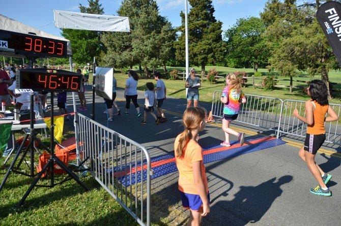 Racers cross the finish line near the Herndon Community Center for the Hendon Festival 5K/10K.