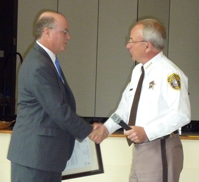 Sheriff Dana Lawhorne, right, congratulates Tony Davis on his retirement as undersheriff at a luncheon held June 3 at the Durant Center.