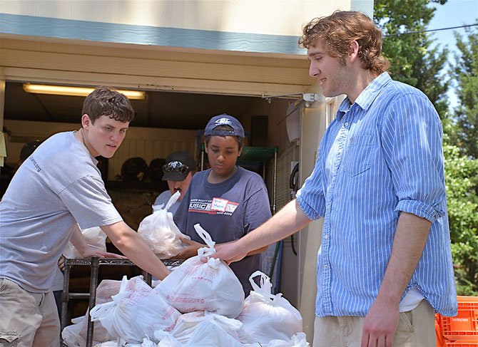 From left, volunteers from South County Cares, Kyle Fischer, Hebron Yohannes and Ian Kraft hand out bags of basic groceries to festival attendees.