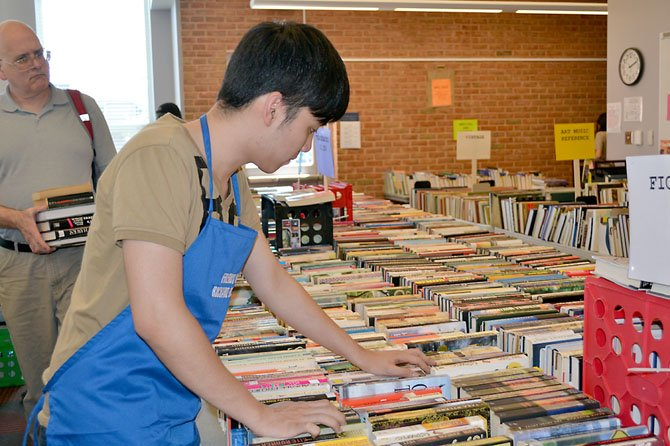 Friends volunteer Bao Nguyen, a college student, makes sure the books are in order for prospective buyers.