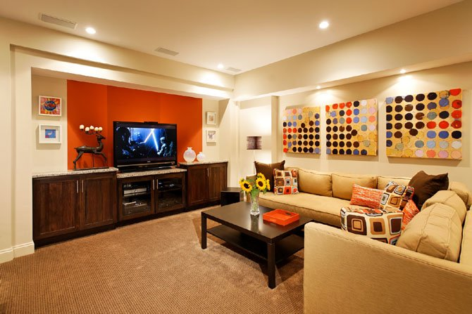Local designers say brightly colored accent walls, such as the orange used in this basement created by Sun Design, is a current trend in interior paint colors.