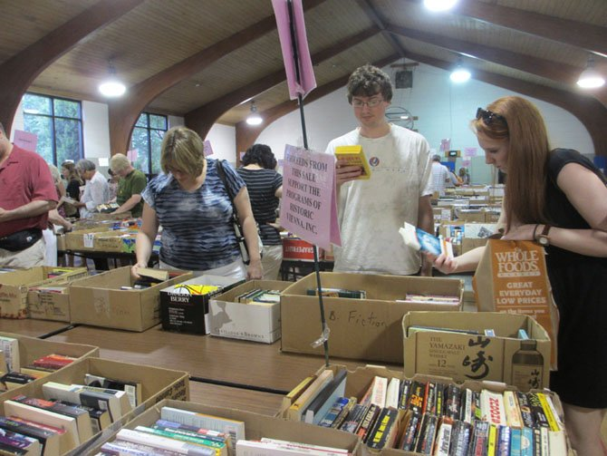 Shoppers take their time looking through the 1,200 boxes of books at Historic Vienna, Inc.'s book sale at the Vienna Community Center.