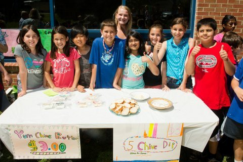 Churchill Road fourth graders Emily Mortman, Arielle Moore, Alewx Zaccardelli, Kevin Kaldes, (fourth grade teacher) Aubrey Beiswenger, Areej Khatri, Jenna Ashtar, Zoe Hendriks and Mazin Khan provide free samples of the chive butter and dip they made from homegrown chive plants at their farmer's market June 4th.