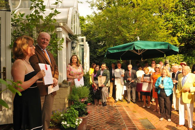 Gretchen Bulova, director of the Gadsby Tavern Museum and the Stabler-Leadbeater Apothecary Museum, accepts a grant for both museums from Historic Alexandria Foundation president Dr. Morgan Delaney at the annual meeting and garden party on Sunday afternoon.