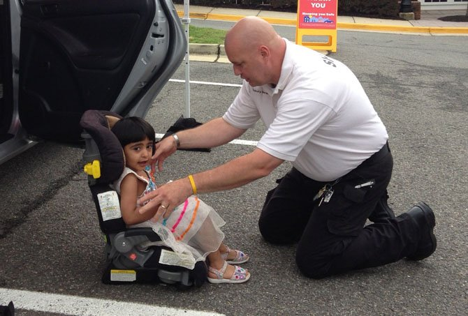 Sheriff Tim Gerard of the Arlington Sheriff's Department checks the fit of a car seat for 3-year-old Aman Rahman, who attends the Center for Alexandria's Children's playgroup.