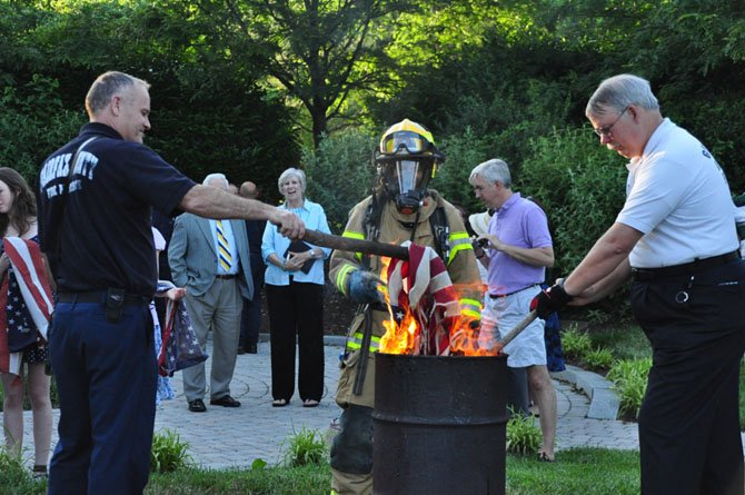 From left, Capt. Michael Allen, firefighter Liezel D'souza and Great Falls Volunteer Fire Chief Frank Smith assist the Children of the American Revolution in their annual Flag Day ceremony, properly disposing of damaged and worn American flags.