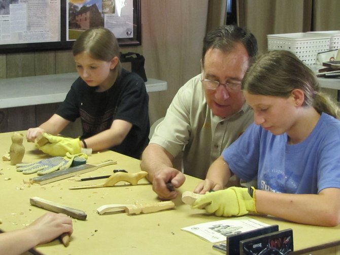 Catherine Edge and Amanda Rutledge watch Mike of Arlington from the Northern Virginia Carvers, as he teaches them the basics of woodcarving.
