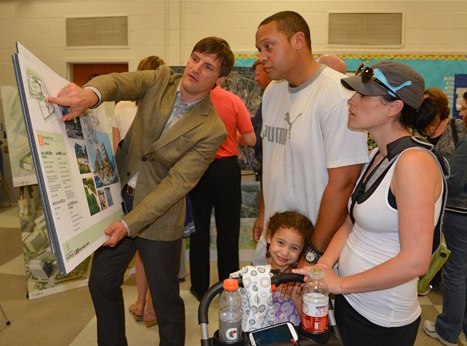 Jay W. Klug, principal with Tysons West developer JBG Rosenfeld, points out the highlights of the mixed-use project to Vienna residents Aaron and Jackie Hughes. Daughter Giuliann wasn't quite as interested as her parents in a new urban-style Walmart currently included in the plans.