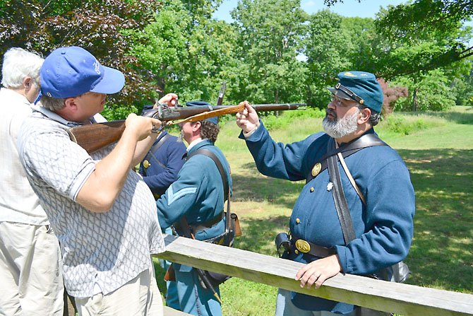 Paul Vaselopulos, right, demonstrates how to use a musket.