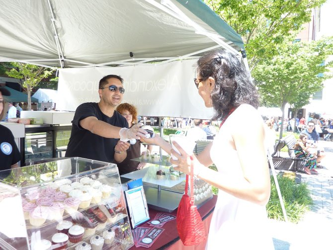Alexandria Cupcake owner Adnan Hamidi serves a cupcake to Eindra Khin Khin during the Alexandria Food and Wine Festival June 22. Hamidi's cupcakes won Best Dessert at the Carlyle-area festival.