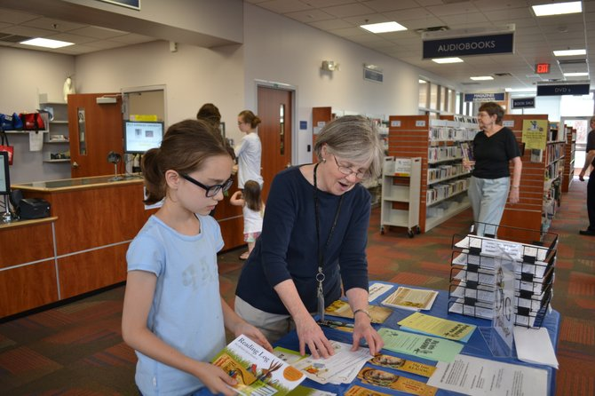 Richard Byrd Library Branch Manager Sally Eckard shows a young reader information about the summer reading program.