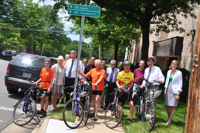 County staff and bicycling advocates gather at one of the new bicycle wayfinding signs in downtown McLean Thursday, June 20.
