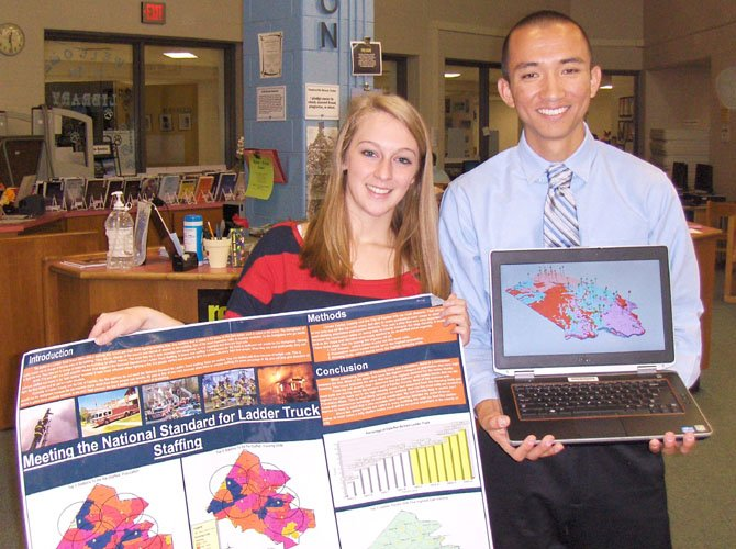 Kelsey Ciarrocca and Steven Yu with a poster of her GMU project and his 3D map showing the locations of Iowa's existing water wells, the rock types and water depths.