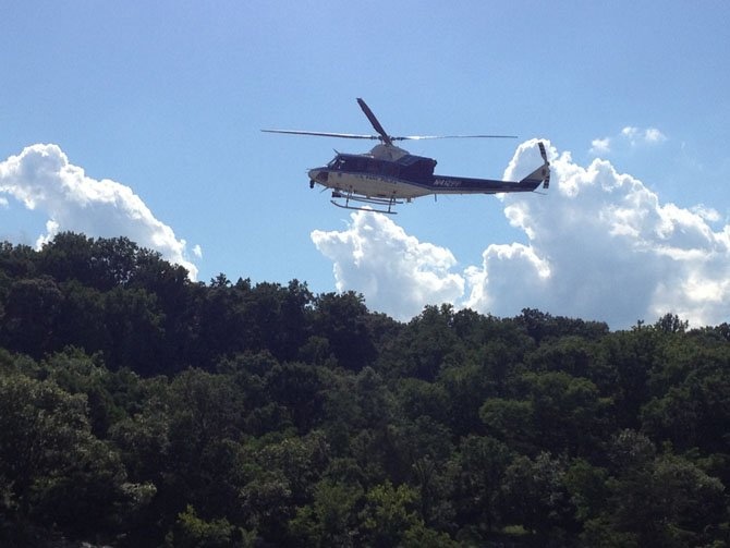 A helicopter flies low through Potomac River gorge searching for a swimmer who didn't make it back to shore.