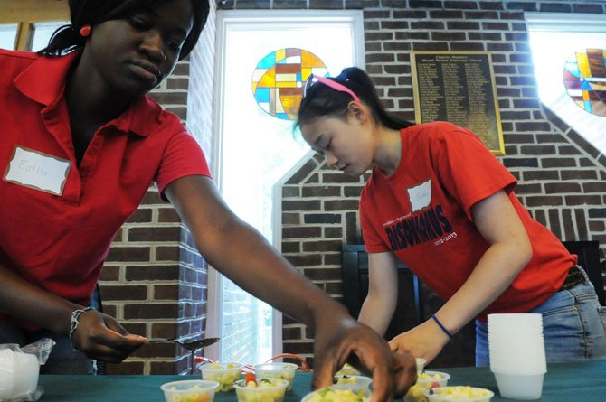 Volunteers Caroline Caplen and Esther Antwiwaa-Bonsu prepare sample of Chef Cathal Armstrong's dish made from the UCM pantry.
