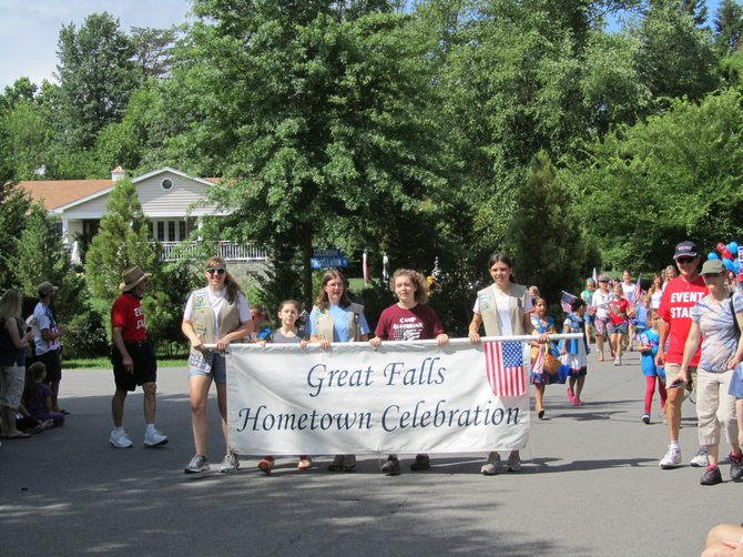 Representatives from several local Girl Scout troops helped lead the parade, carrying the banner and waving dozens of American flags. Girl Scouts of all ages participated in the event.
