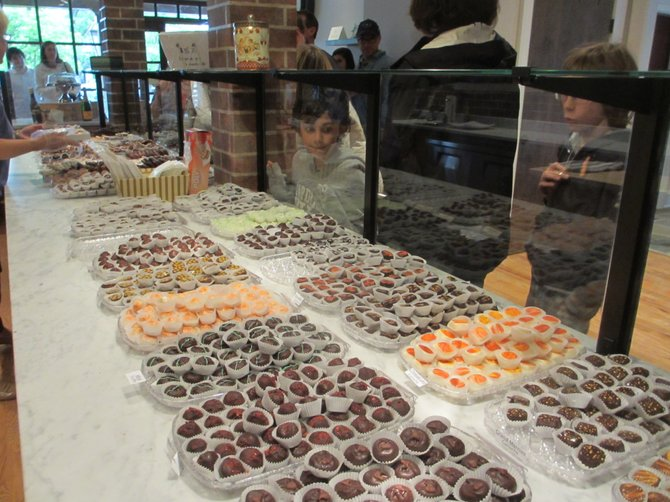 A child peers behind a glass barrier at the counters laden with chocolates at Cocoa Vienna.